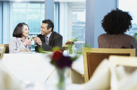 motioning: Businessman and a businesswoman toasting wine in a restaurant