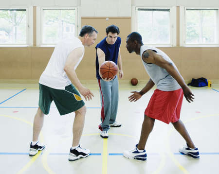 Two young men and a mid adult man playing basketball in the basketball court