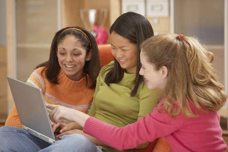 hairband: Three teenage girls using a laptop