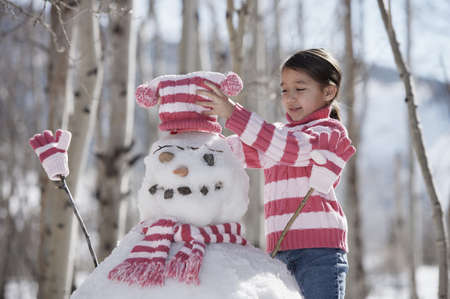 bobble: Girl putting a bobble hat on a snowman