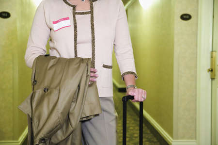 pacific islander ethnicity: Mid section view of a mid adult woman standing in a hotel corridor