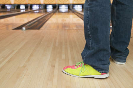 low section view: Low section view of a young person standing in a bowling alley LANG_EVOIMAGES