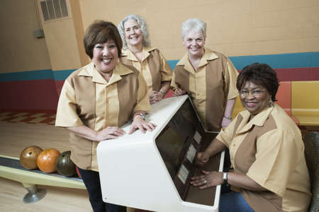 Portrait of four mature women smiling in a bowling alley
