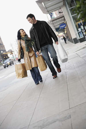 mid adult couple: Mid adult couple walking with shopping bags