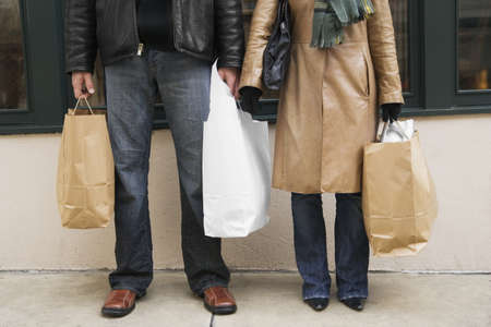 mid adult couple: Low section view of a mid adult couple holding shopping bags