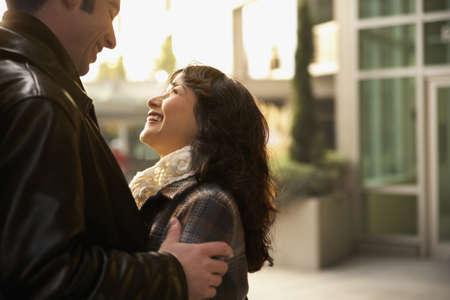mid adult couple: Perfil lateral de una pareja abrazada a mediados de adultos