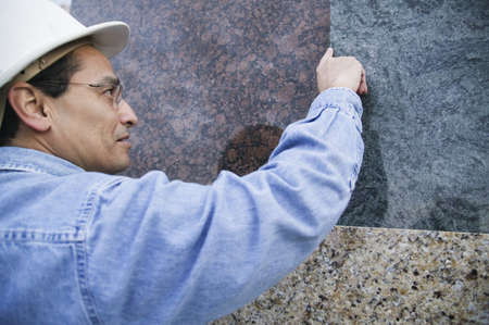 receding hairline: Rear view of a male construction worker touching a granite sheets edge LANG_EVOIMAGES