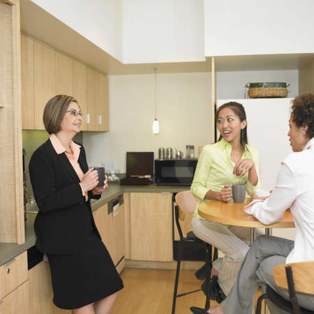 mujer tomando cafe: Tres mujeres que beben el caf� en la cocina