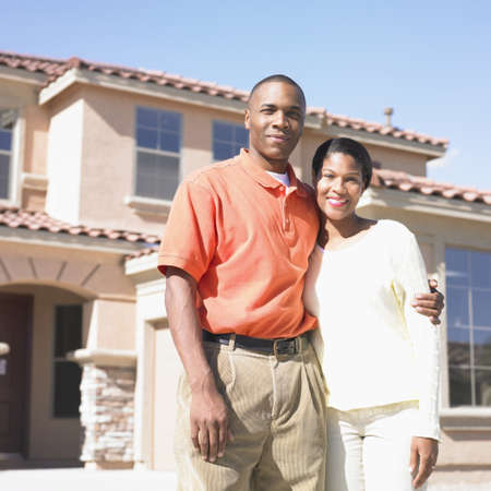 mid adult couple: Portrait of a mid adult couple standing in front of a house LANG_EVOIMAGES