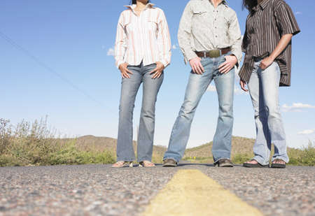 Low angle view of two young women and a young man standing on the road LANG_EVOIMAGES
