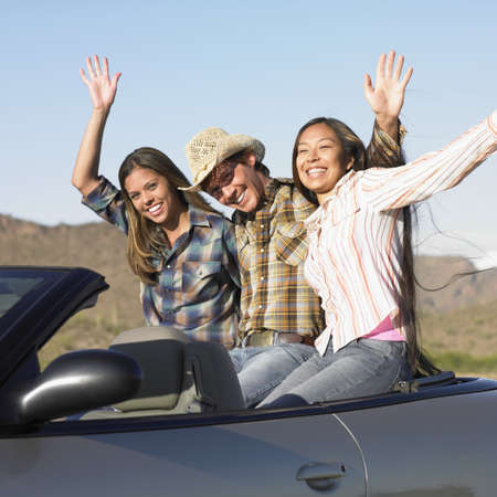 only three people: Portrait of a young man and two young women sitting in a convertible car