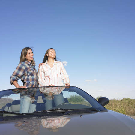 rolled up sleeves: Two young women standing in a convertible car LANG_EVOIMAGES