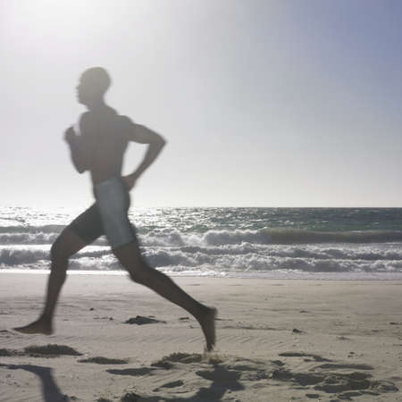 adult footprint: Side profile of a young man running on the beach