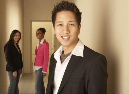 chinese american ethnicity: Portrait of a businessman smiling with two businesswomen standing behind him LANG_EVOIMAGES