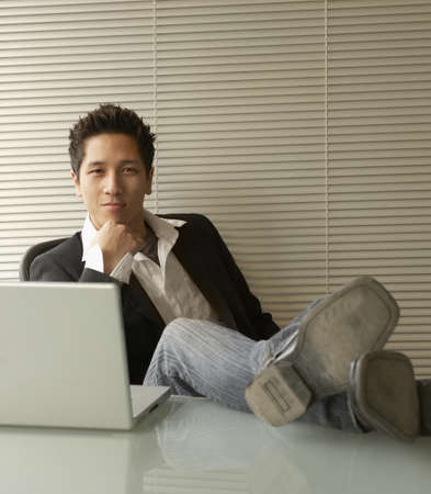 spiky hair: Portrait of a young man sitting in front of a laptop with his hand on his chin