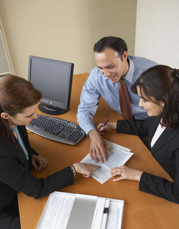 High angle view of a businessman and two businesswomen discussing in an office