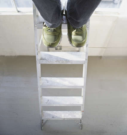 low section view: Low section view of a young man standing on a step ladder