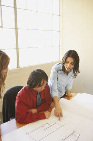 Two businesswomen and a businessman discussing blueprints in an office Stock Photo