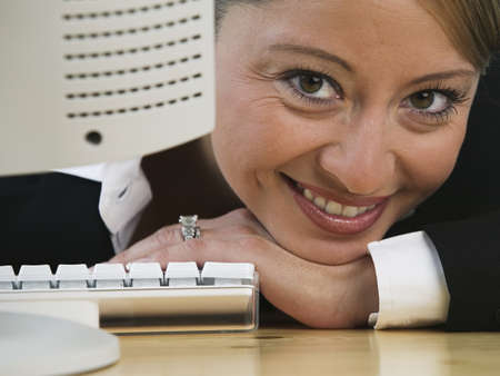 Portrait of a businesswoman sitting in front of a computer smiling LANG_EVOIMAGES