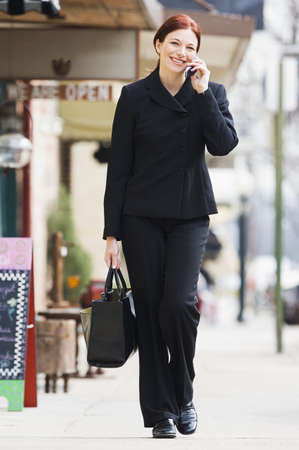 familial affection: Businesswoman walking on a walkway and talking on a mobile phone