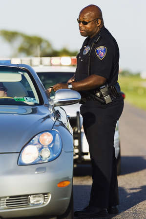 transportation: Police officer taking the drivers license of a mid adult woman LANG_EVOIMAGES