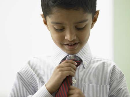indian child: Close-up of a boy adjusting his tie LANG_EVOIMAGES