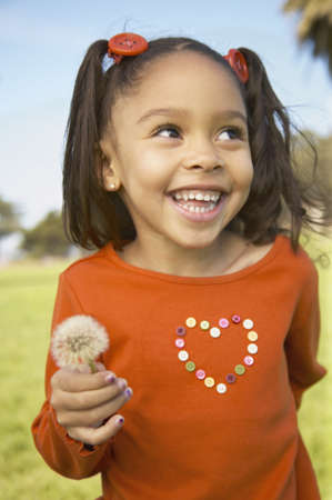niños negros: Primer plano de una niña con una flor en un césped