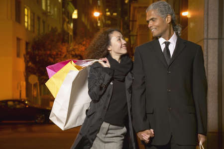 confiding: Mid adult woman walking with mature man holding shopping bags