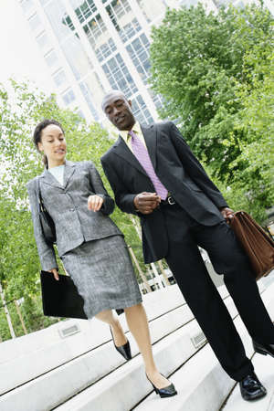 descending: Businesspeople descending steps together LANG_EVOIMAGES