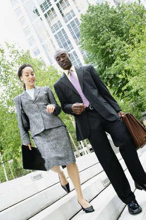 descending: Businesspeople descending steps together LANG_EVOIMAGES