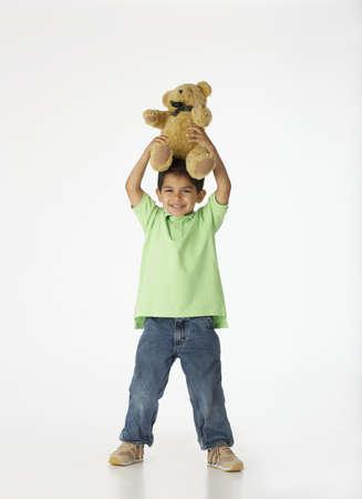 all under 18: Boy holding teddy bear on top of head