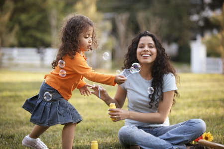 diverse family: Mother and daughter blowing bubbles outdoors