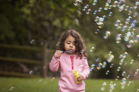 kids playing: Girl outdoors blowing bubbles