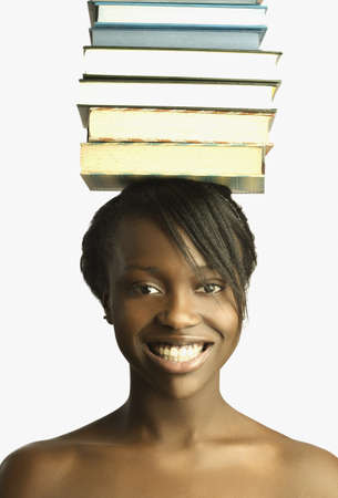 Young woman balancing books on head