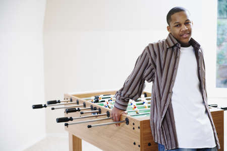 foosball: Boy standing beside foosball table LANG_EVOIMAGES