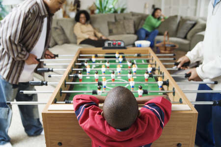some under 18: Family watching foosball game LANG_EVOIMAGES
