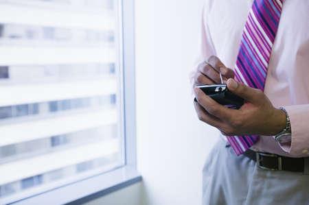 hand held: Uomo d'affari con dispositivo portatile LANG_EVOIMAGES