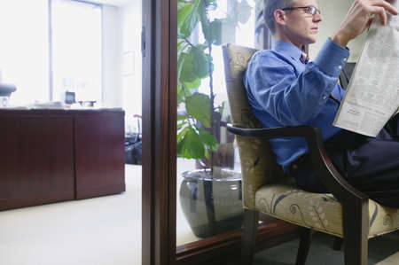 above 30: Businessman reading newspaper