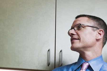 brooding: Headshot of businessman near cabinets