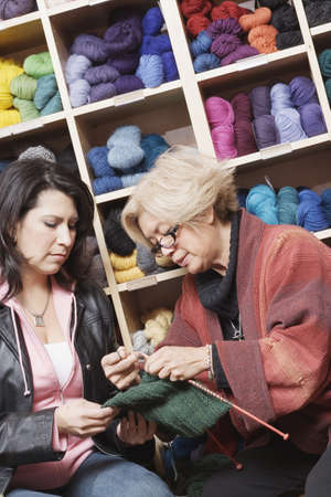 taking inventory: Woman knitting in front of yarn