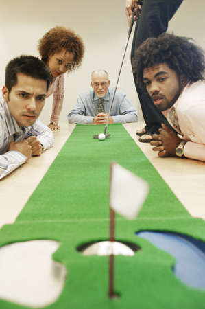 jamaican adult: Colleagues playing golf in a conference room