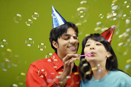 blowing bubbles: Couple wearing party hats blowing bubbles