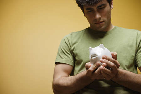 spanish ethnicity: Young man holding piggy bank