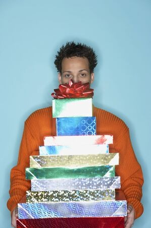 french ethnicity: Young man behind stack of gifts LANG_EVOIMAGES