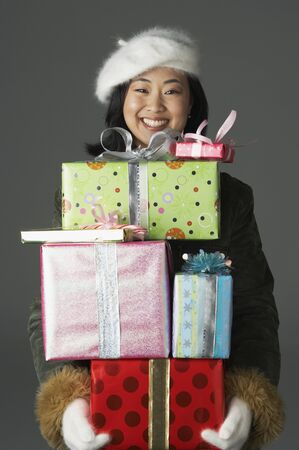 saint nick: Young woman with stack of gifts LANG_EVOIMAGES