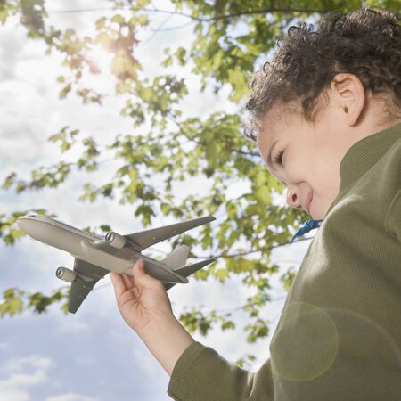 all under 18: Boy standing outside with toy plane