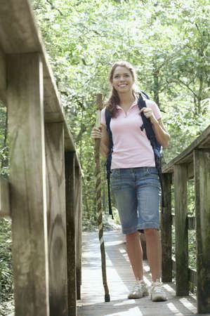 leaning by barrier: Young woman standing on a walkway