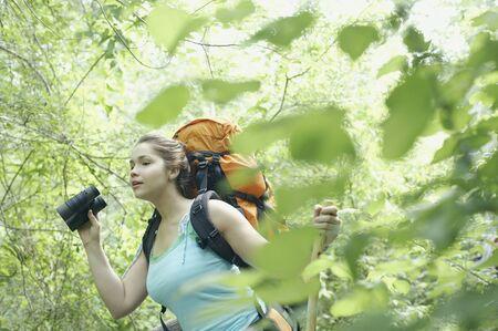 using binoculars: Young female hiker using binoculars