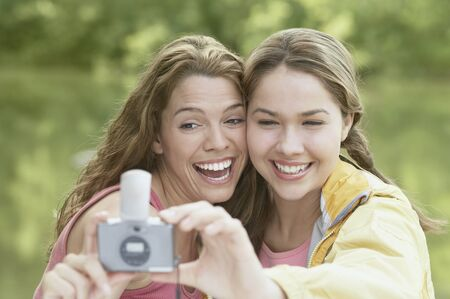 vivacious: Women taking snapshots in a forest LANG_EVOIMAGES