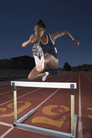 lean machine: Female track athlete clears a hurdle LANG_EVOIMAGES
